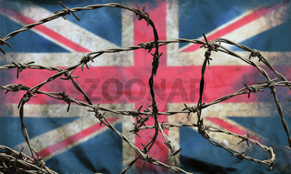 barbed wire in front of an old stained dirty union jack british flag with dark crumpled edges brexit freedom of movement isolationist concept