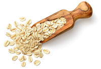 raw oatmeal in the wooden scoop, isolated on white, top view
