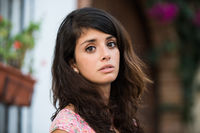 Portrait of a young woman in a tipical spanish yard looking into the camera.