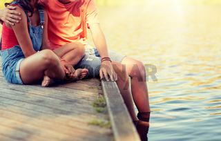 happy teenage couple sitting on river berth
