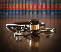 Gavel and Stethoscope on Wooden Table With Law Books In Background