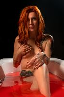 Red-haired nude woman in bloody bath shot