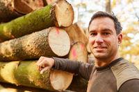 Forstwirt lehnt an Stapel mit Baumstämmen