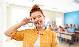 red haired student girl showing peace at school