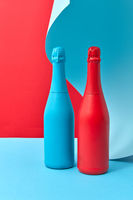 Wine bottles mock-up painted red and blue on a duotone curly background.