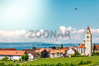 Panoramic view of lake of Lake Constance. Zeppelin and Catholic Church St. Johann Baptist in Hagnau on the picture.