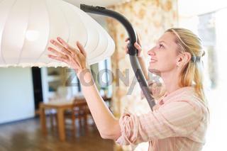 Putzfrau beim Staubsaugen an einer Hängelampe
