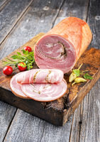 Traditional Allgauer veal roast roll sausage sliced and as piece with tomatoes and chili as closeup on an old rustic cutting board