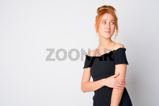 Portrait of young beautiful redhead woman thinking