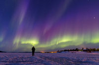Person watching a breath-taking display of colorful northern lights on frozen lake Inari, Finland.