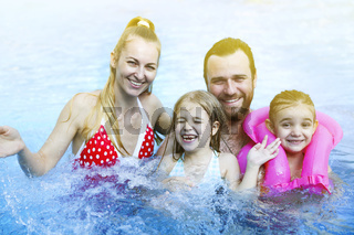 Happy family with children in the pool