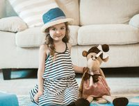 Portrait of adorable little girl sitting on carpet.