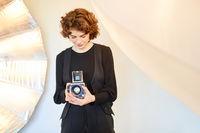 Junge Fotografin kontrolliert Kameraeinstellungen