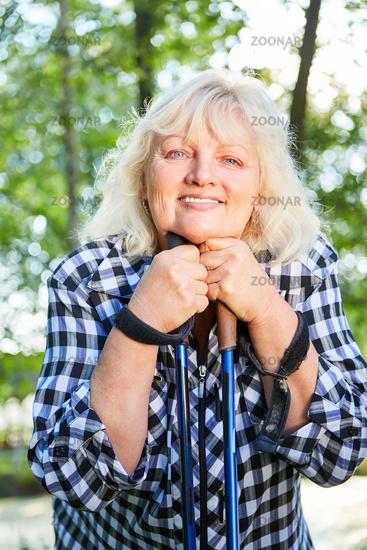 Zufriedene Seniorin mit Nordic Walking Stöcken