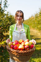Pretty Woman holds basket with organic Apples