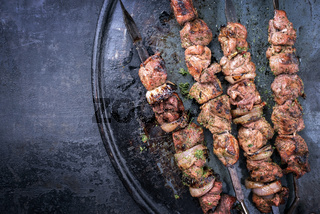 Traditional Russian shashlik on a barbecue skewer with roasted onion as top view on old board with copy space left