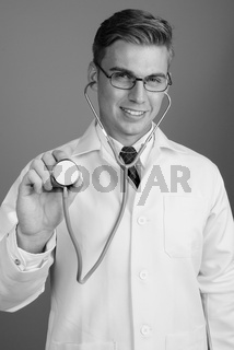 Portrait of young handsome man doctor with eyeglasses in black and white