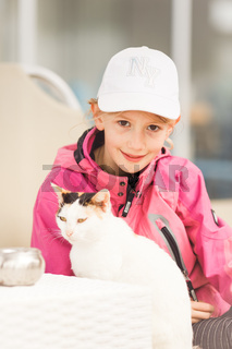 Young blond girl, primary school age, wearing sun cap, caressing cat lying on sunbed