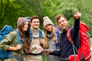 friends or travelers hiking with backpacks and map