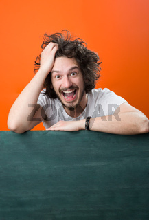 handsome young man with chalkboard plane on color background, copy space on chalkboard surface
