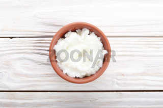 Coconut oil in brown clay bowl on white wooden kitchen table