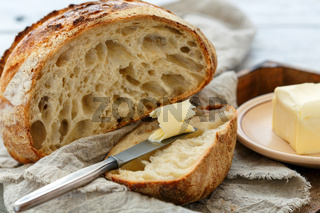 Hunk of French artisanal bread and a knife with butter.