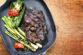 Barbecue dry aged wagyu entrecote beef steak with vegetable and herbs as top view on a gray cast iron pan with copy space right