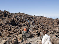 Tourists walking through stones and volcanic rocks