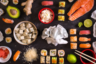 Sushi and ingredients on dark background