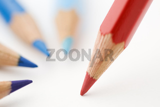 three blue and one red pencils near