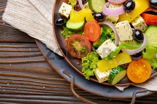 Top view at Mediterranean diet dish greek salad on vintage metal tray