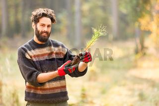 Förster Azubi pflanzt Setzling für Nachhaltigkeit