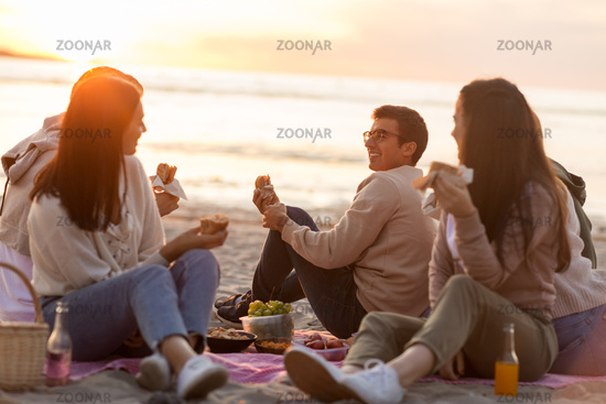 happy friends eating sandwiches at picnic on beach
