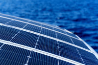 Close up view part of solar panel on dock of sailboat and blue sea waters during sunny day outdoors
