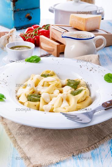 Tortellini di formaggio with basil pesto and cheese sauce