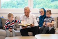 modern muslim grandparents with grandchildren reading Quran