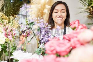 Asiatische Frau als Floristin mit vielen Blumen