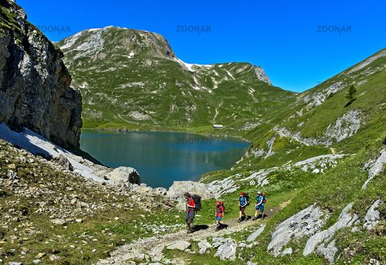 Hikers at the mountain lake Iffigsee, Lenk, Switzerland