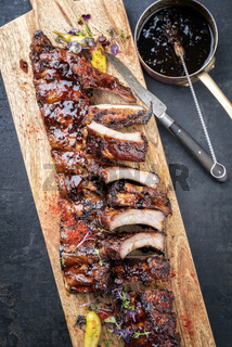 Barbecue spare ribs St Louis cut with hot honey chili marinade and chili as top view in a wooden cutting board