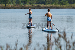 Two women stand up paddleboarding