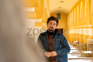 Portrait of a stylish handsome young man with a jaket outdoors.  A serious man wearing a denim jacket looking confident at the camera