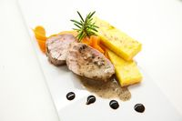 Polenta, roasted pork and rosemary with balsamic reduction on a white plate