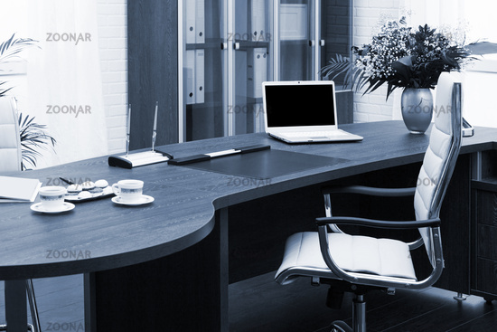 laptop and flowers on table in a modern office