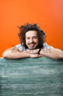 handsome young man with rustic plane on color background, copy space on rustic surface