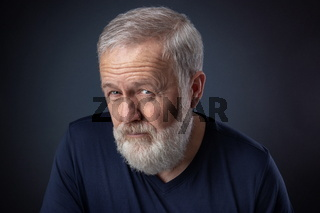 Old man with gray beard looking suspicious