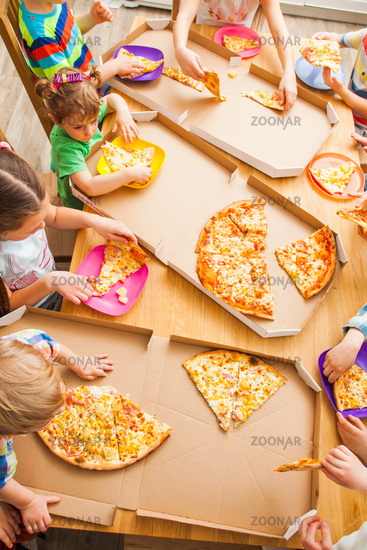 Top view image of children take slices of pizza from box at the kitchen.