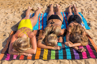 Three blonde girls sunbathing on beach