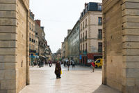 view through the Porte Guillaume Arch in Dijon with a Muslim woman