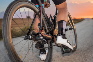 Low angle view of cyclist standing with bike at sunset