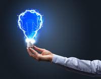 Hand holding shiny light bulb